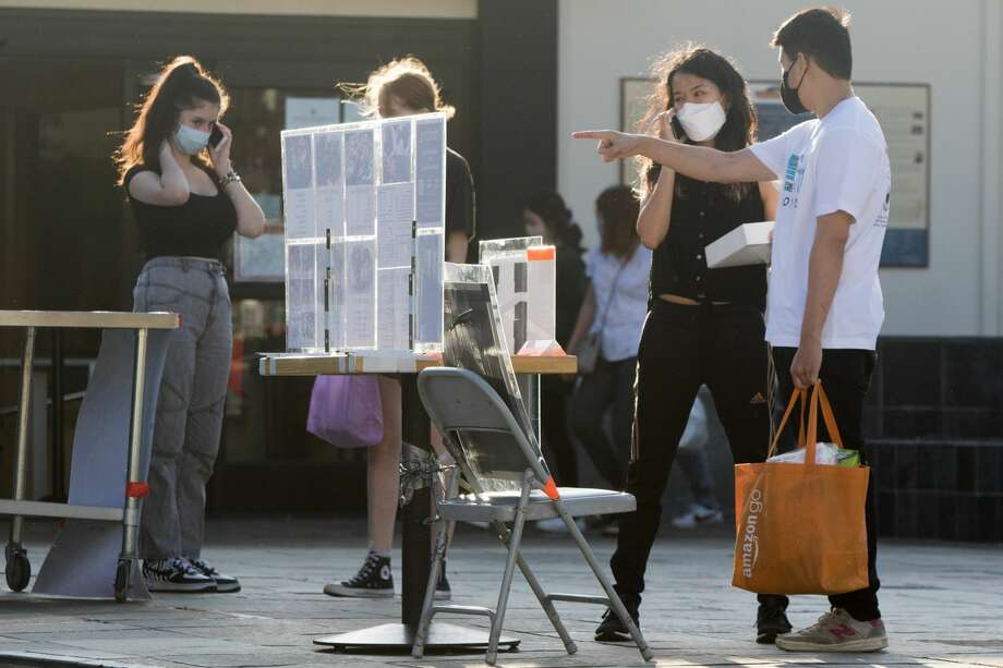 Customers look at takeout menus located in the Peace Plaza to order from restaurants on Aug. 18, 2020. Restaurants inside the Japan Center malls have had to resort to takeout services, many located at tents set up on the center's plaza. Photo: Douglas Zimmerman/SFGATE / SFGATE