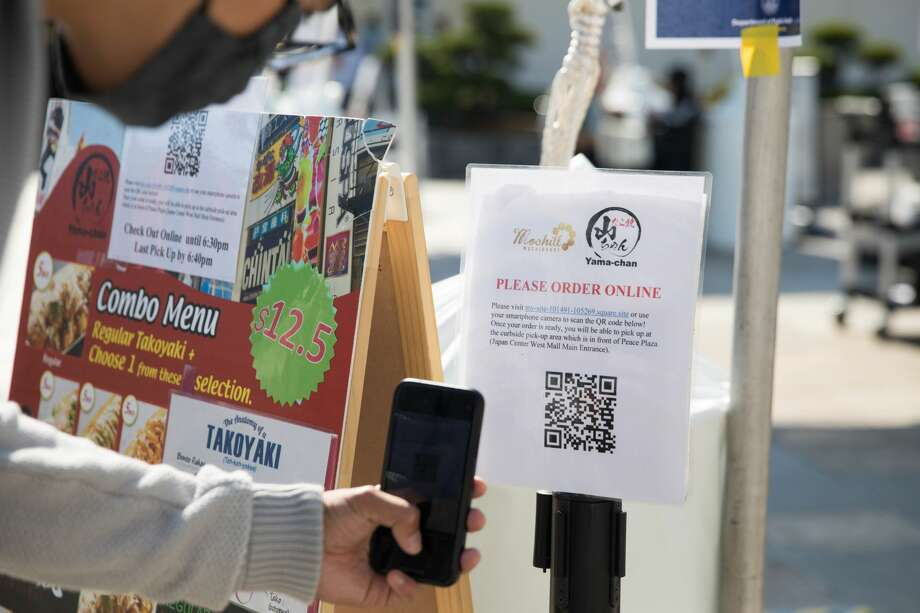 Kyle Young scans a QR code for Mochill Donuts' menu to fill out an order online on the Peace Plaza on Aug. 21, 2020. Because the Japan Center malls have been closed to the public, restaurants inside are offering takeout services at tents set up on the center's plaza. Photo: Douglas Zimmerman/SFGATE / SFGATE