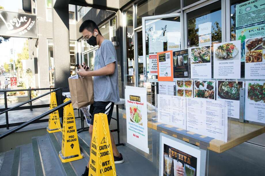An Uber Eats delivery driver grabs a takeout order from a Japantown restaurant on Aug. 18, 2020. Restaurants inside the Japan Center malls have had to resort to takeout services, many located at tents set up on the center's plaza. Photo: Douglas Zimmerman/SFGATE / SFGATE