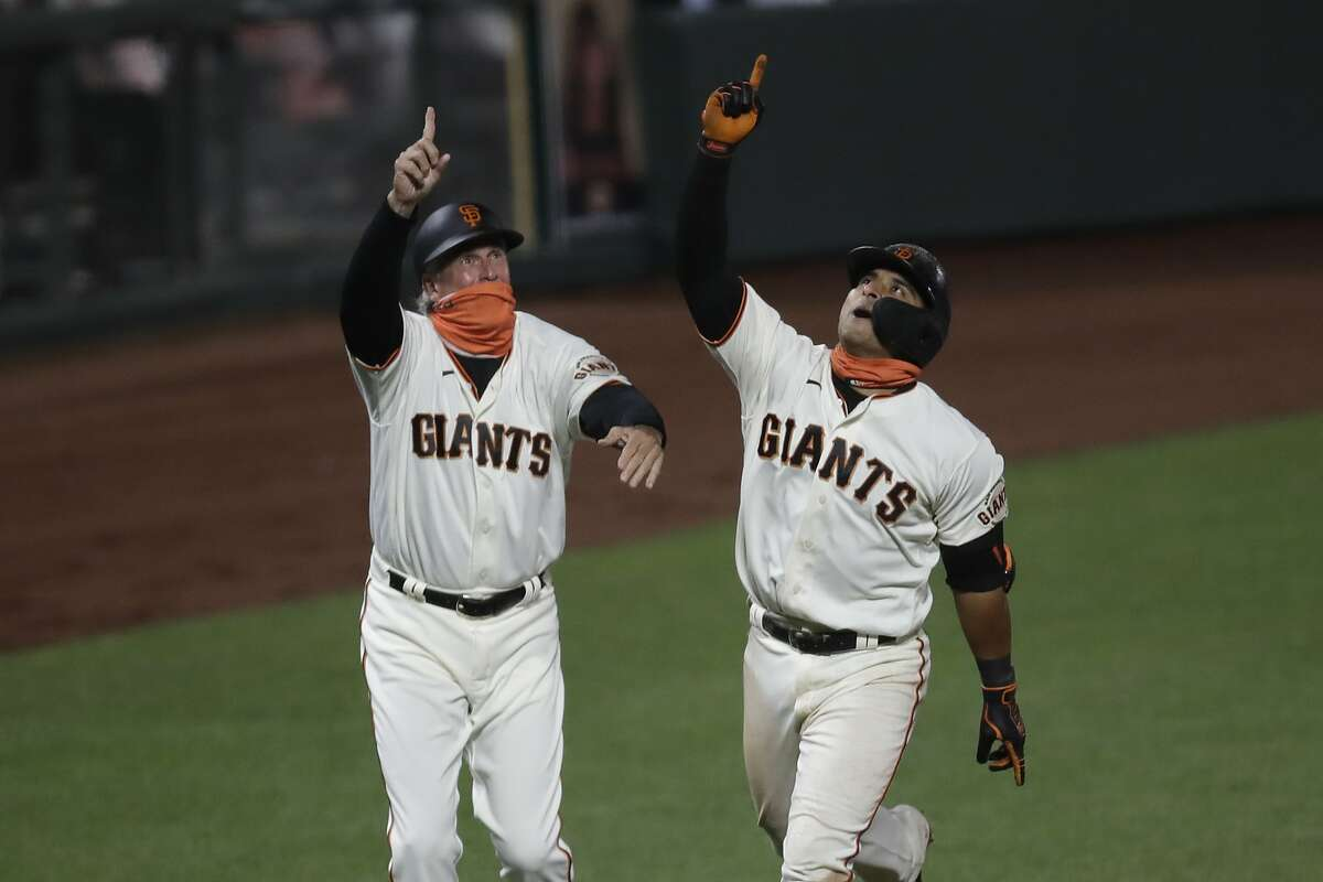 San Francisco Giants' Donovan Solano, right, celebrates with third base coach Ron Wotus after hitting the game winning home run against the Los Angeles Dodgers in the eleventh inning of a baseball game Tuesday, Aug. 25, 2020, in San Francisco. (AP Photo/Ben Margot)