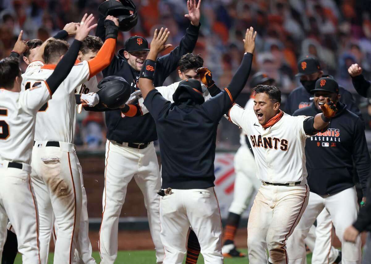 Donovan Solano #7 of the San Francisco Giants is congratulated by teammates after he hit a walk off home run to win the game in the 11th inning against the Los Angeles Dodgers at Oracle Park on August 25, 2020 in San Francisco, California.
