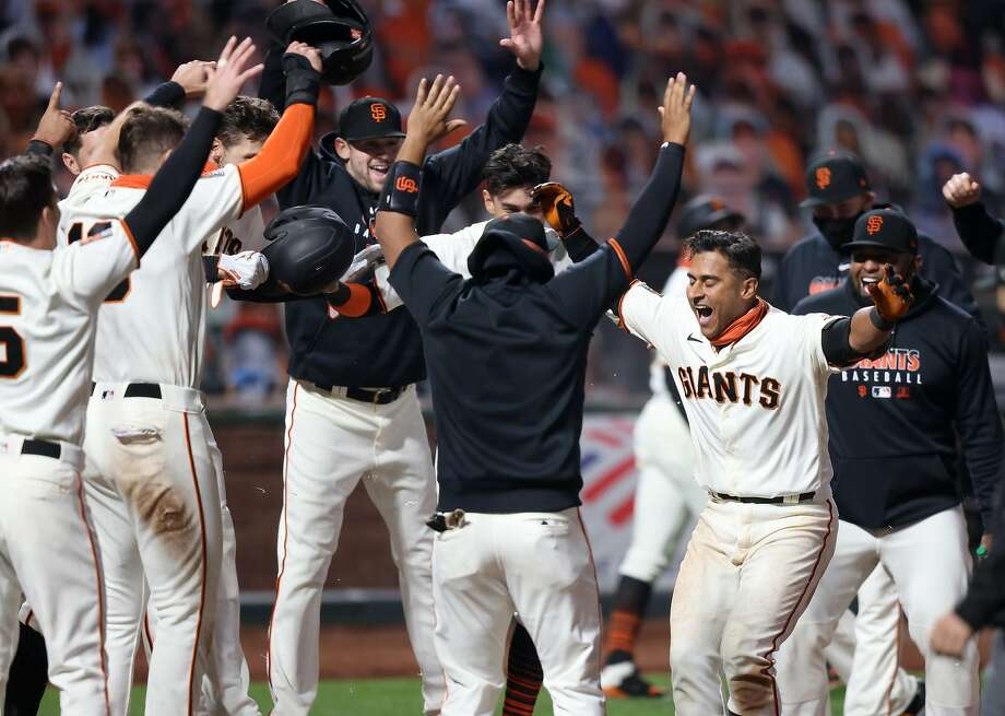 Donovan Solano #7 of the San Francisco Giants is congratulated by teammates after he hit a walk off home run to win the game in the 11th inning against the Los Angeles Dodgers at Oracle Park on August 25, 2020 in San Francisco, California. Photo: Ezra Shaw, Getty Images