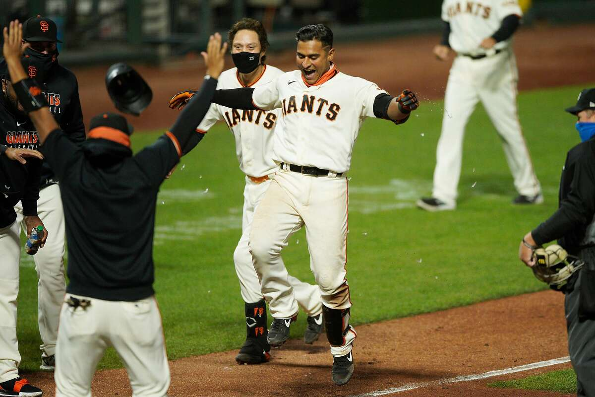San Francisco Giants shortstop Donovan Solano (7) hops to home plate after his two-run home run to win the game against the Los Angeles Dodgers in the 11th inning during an MLB game at Oracle Park on Tuesday, Aug. 25, 2020, in San Francisco, Calif. The Giants won 10-8 in the bottom of the 11th inning.