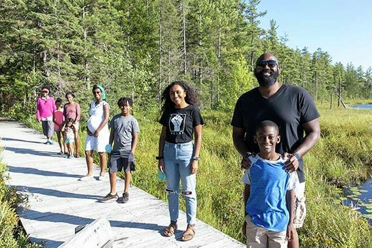 From right to left, Clifton H. Harcum, Clifton Harcum, Jr., Jada Meadows, Yosef Spear, Bianca Black, Temnit Muldowney, Talia Muldowney, Ella Muldowney, and Nicole Hylton-Patterson pose for a photo at the Paul Smith's College's VIC during a hike organized by the Adirondack Diversity Initiative.