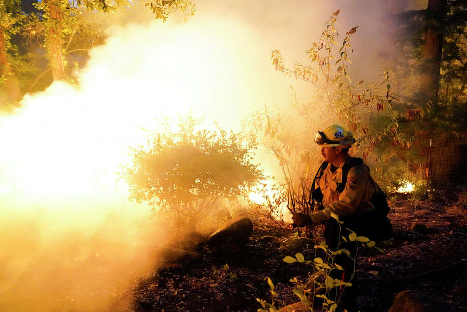 Firefighter Jeremy Damon of the Nevada Yuba Placer Fire Dept. monitors a controlled burn in the backyard of a home in front of the advancing CZU August Lightning Complex Fire Friday, Aug. 21, 2020, in Boulder Creek, Calif. (AP Photo/Marcio Jose Sanchez) Photo: Marcio Jose Sanchez/AP / Copyright 2020 The Associated Press. All rights reserved.