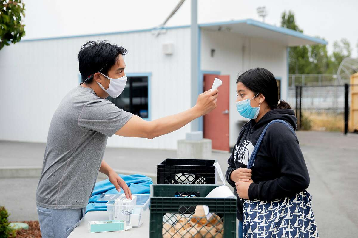 Alberto Deleon checks a student's temperature as she arrives to attend Freedom School, a six-week summer academic enrichment program for Marin County students held at Bayside Martin Luther King Jr. Academy in Marin City, Calif. Tuesday, June 23, 2020. Sausalito and Marin City schools have implemented safety measures such as temperature checks, providing masks and keeping six feet of distance in order to bring kids back for summer school programs. They hope to bring students back in the fall using these same precautions.