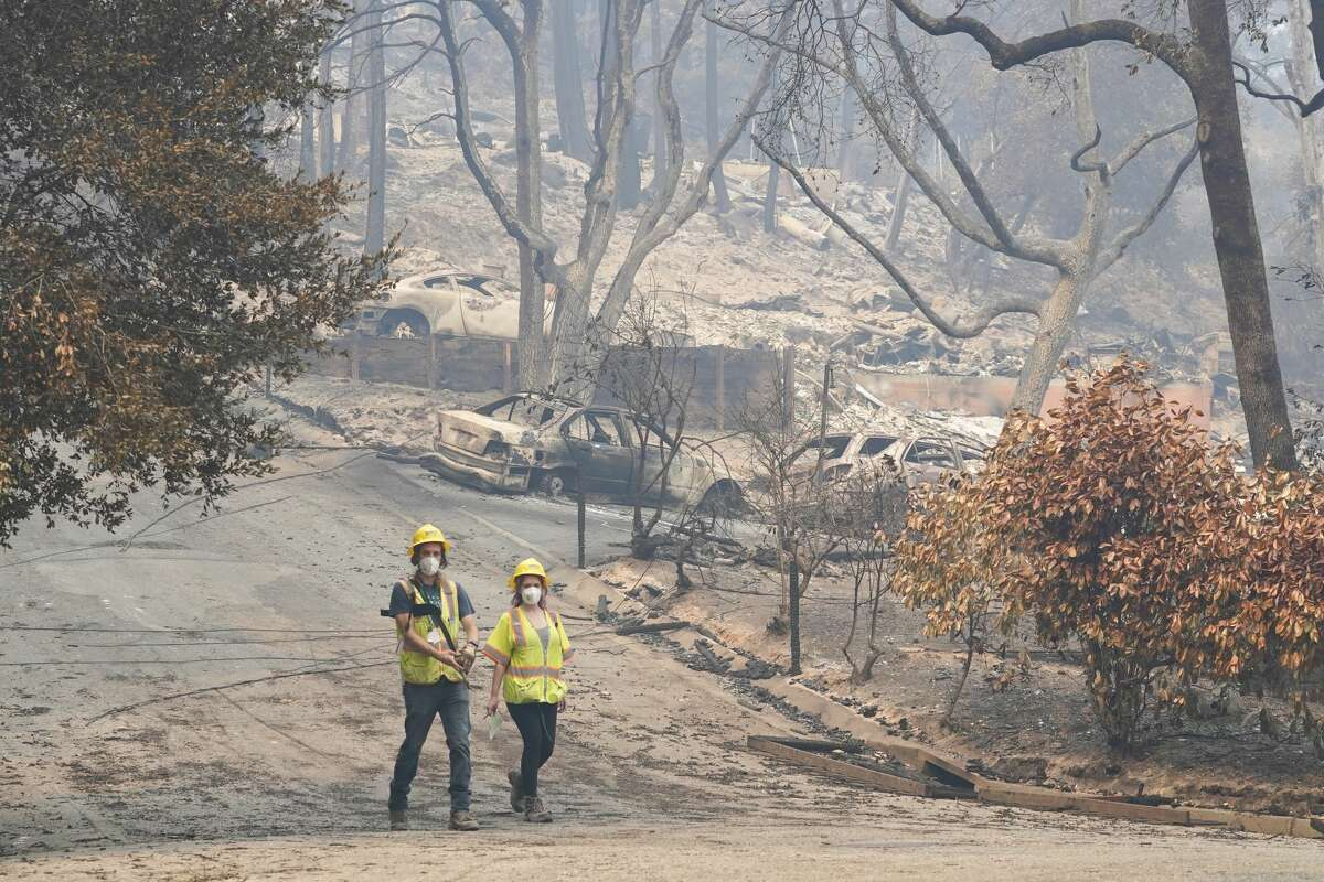 Workers with Davey Resource Group asess the damage to the trees in a neighborhood Tuesday, Aug. 25, 2020, in Boulder Creek, Calif.,after the the CZU August Lightning Complex Fire passed by.