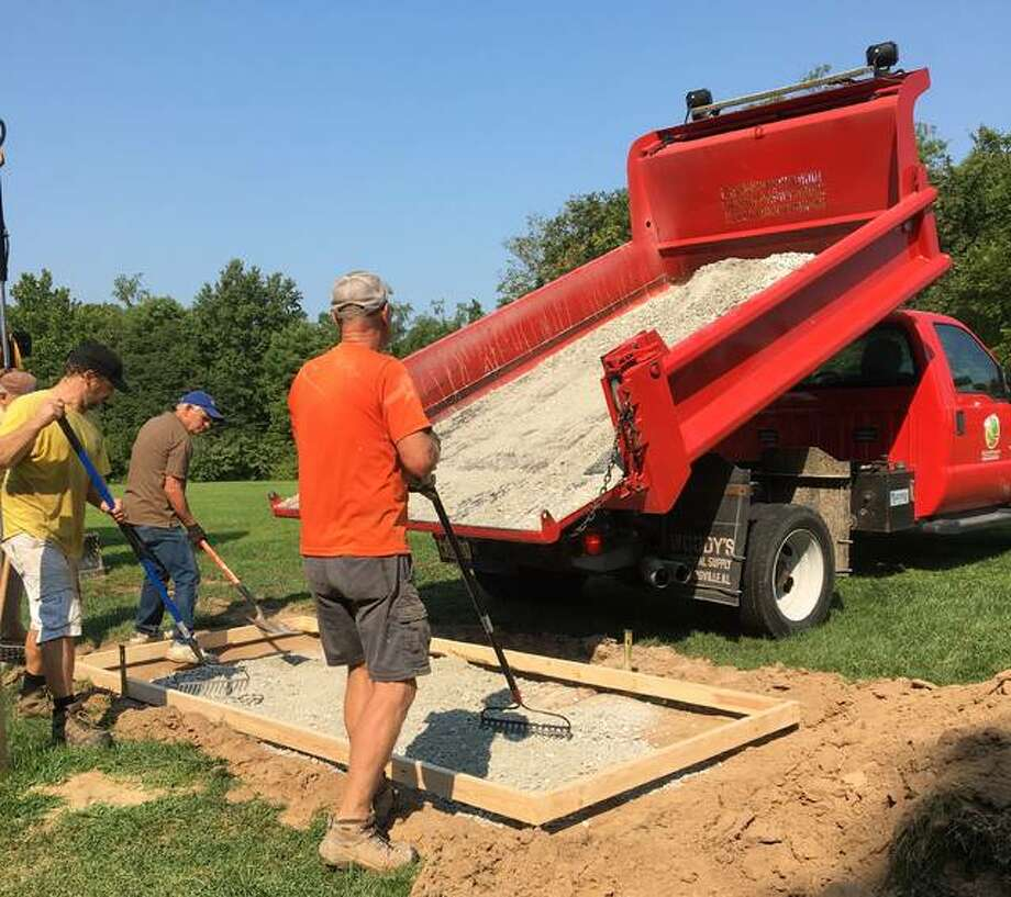Alton-Godrey Rotary Club members Dennis Wilson, Jim White and Tracy Shaffer prepare a disc golf tee box at La Vista Park in Godfrey. Work will continue on the 18-hole course into September.