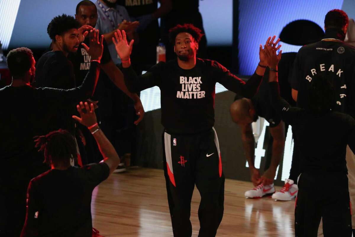 Houston Rockets forward Robert Covington, center, is greeted by teammates during player introductions before an NBA basketball game against the Philadelphia 76ers, Friday, Aug. 14, 2020, in Lake Buena Vista, Fla. (Kim Klement/Pool Photo via AP)