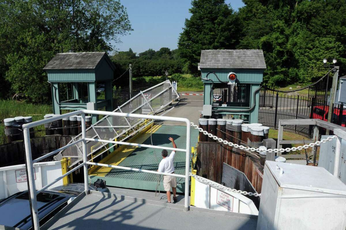 The first mate lifts the gate to allow exiting of The Selden III Chester-Hadlyme Ferry on the Chester side.