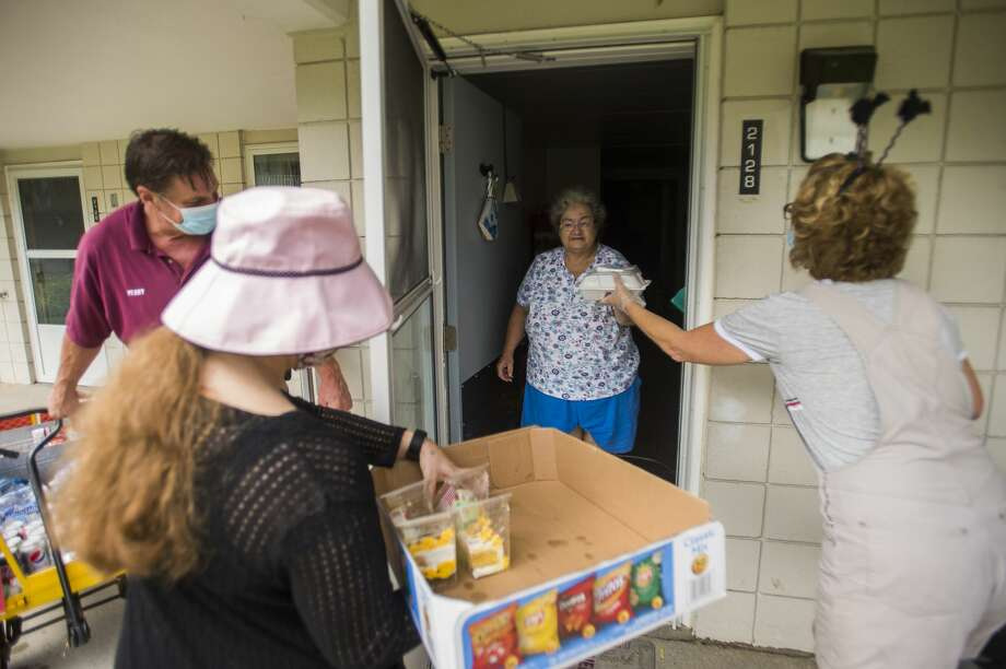 Cleveland Manor Administrative Assistant Marilyn Rease, right, delivers a meal to resident Sandra Johnson, center, during a picnic parade with help from Perry Nunnari, left, and Alexandria Dodge, second from left, Wednesday, Aug. 26, 2020 at the apartment complex in Midland. The facility normally holds a more traditional annual picnic in the courtyard, but made adjustments this year due to COVID-19. (Katy Kildee/kkildee@mdn.net) Photo: (Katy Kildee/kkildee@mdn.net)
