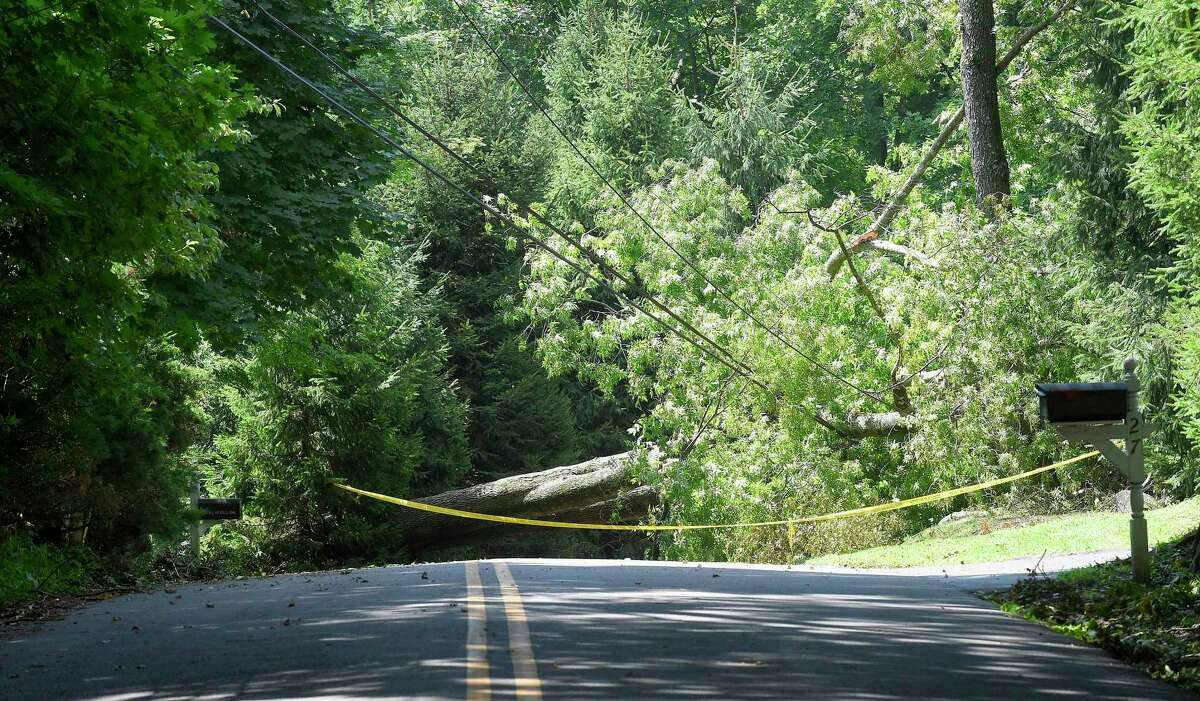 Caution tape warns of potential live wires as a fallen tree blocks the roadway of Hemlock Lane on August 8, 2020 in Greenwich, Connecticut.
