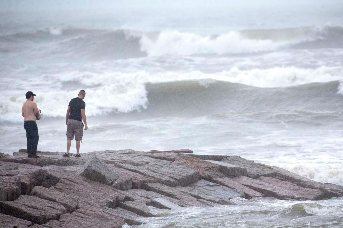 Alex Mazzucco, left, and Nathan Wilson stand out on a jetty watching the surf stirred up by Hurricane Laura on Wednesday, Aug. 26, in Galveston.
