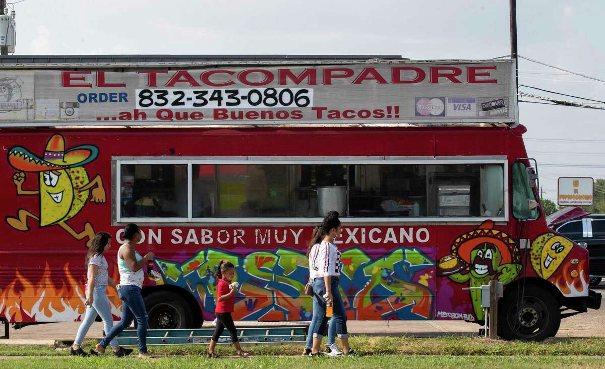 People move past a food truck while walking along Gulfton Street on Thursday, July 16, 2020, in Houston. The coronavirus is raging through Hispanic communities in the Houston area, and two of the five ZIP codes with the highest positivity rates are in Gulfton and Sharpstown neighborhoods.
