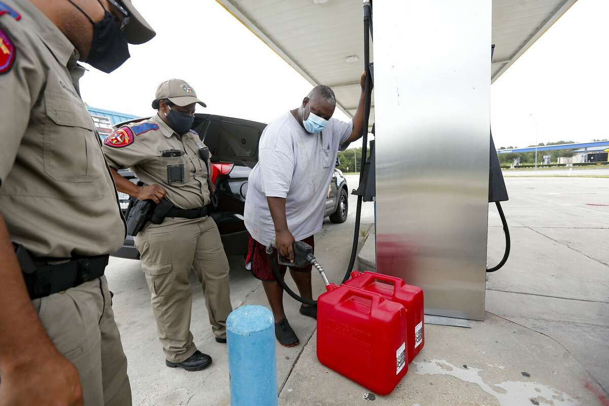 Peter Thomas of West Orange, Texas fills up gas cans in Bridge City, Texas under the watchful eye of his wife, Trooper Pamela Thomas on Wednesday, Aug. 26, 2020.