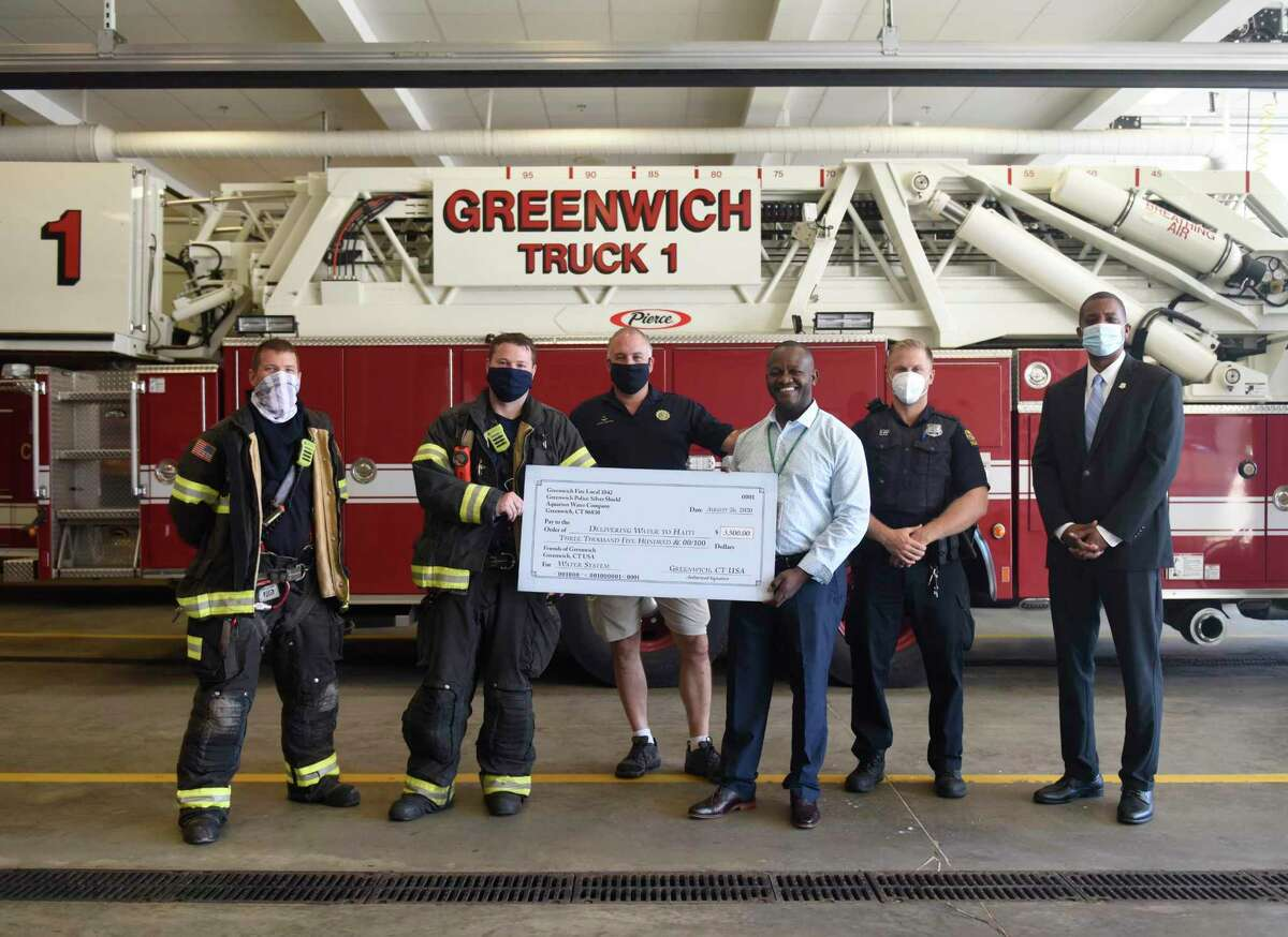 From left, firefighter Dustin Holt, firefighter Doug Howley, Fire Captain Jim Bonney, Public Safety Complex maintenance worker Jonas Dorélus, police officer Ryan Carino, and Aquarion Director of Public Relations George Logan pose with a check to be used for a water well to be built in Dorélus' hometown in Haiti at the Public Safety Complex fire department in Greenwich, Conn. Wednesday, Aug. 26, 2020. Made possible with donations from Aquarion Water Company, Greenwich Fire Local 1042, and Greenwich Police Silver Shield, the $3,500 check will be used to built a well in Marmonc, Haiti.