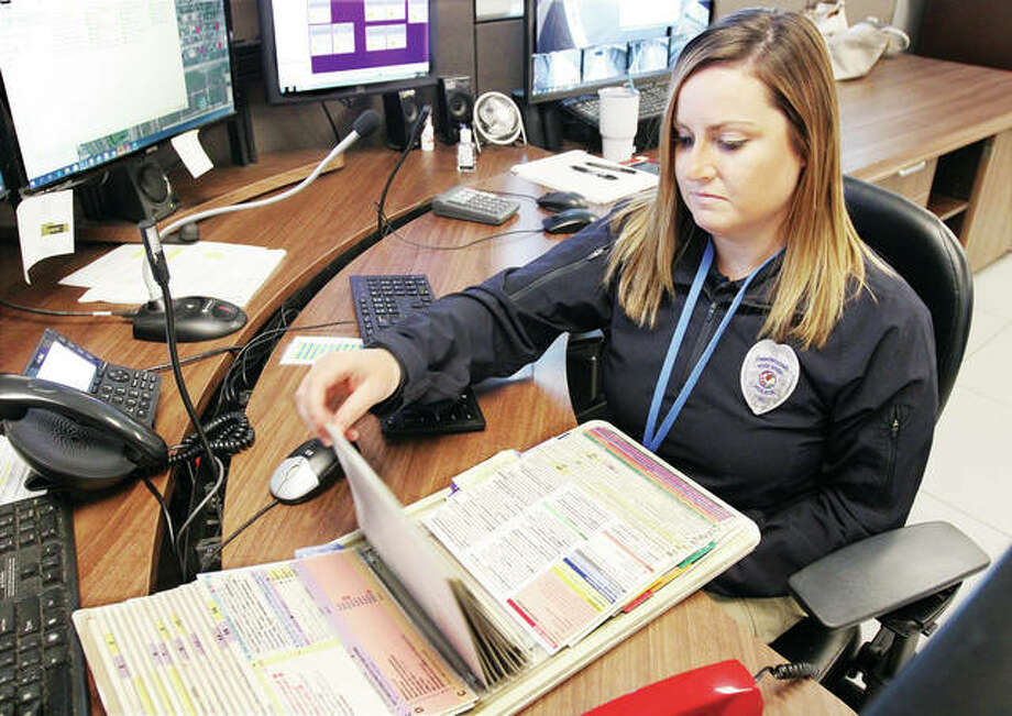 Kacey Hill. a telecommunicator at the Wood River 911 Center, looks through the office's Medical Flip Book. The Emergency Telephone System Board has approved spending $368,979 over five years for a new system calledProQA.