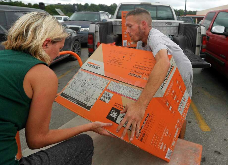 Chaz Barnett and his wife, Kirsty, load a pair of generators into his truck for their family and their in-laws, Wednesday, Aug. 26, 2020, in Porter. Hurricane Laura, a Category 4 storm, is projected to make landfall Wednesday evening along the Texas-Louisiana border. Photo: Jason Fochtman, Houston Chronicle / Staff Photographer / 2020 © Houston Chronicle