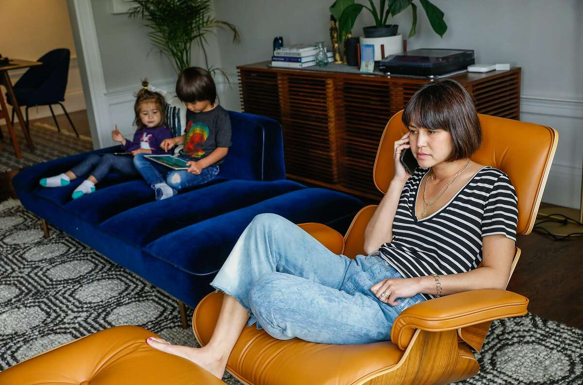 (L-r) Eliette Seeger, 2, and her brother Graham Seeger,4, relax on their iPads while mom Jenny Seeger listens to work voicemails at their home on Thursday, April 16, 2020 in San Francisco, California. Before the shelter in place took effect due the the coronavirus the Seeger�s used to only allow their children 30-minutes of screen time. Now that they are working from home in quarantine they�ve had to extend the use of iPad�s and television to several hours to get their work done.