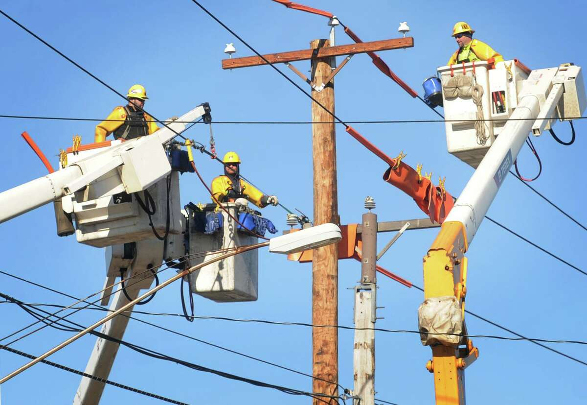 A file photo of a United Illuminating crew working on utility poles in 2016.
