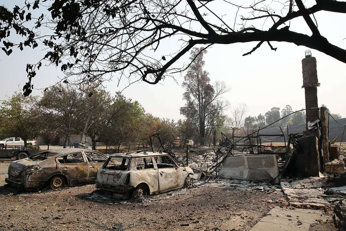 Charred vehicles rest in a driveway at a burned down home off of English Hills Rd. in Vacaville, Calif., on Wednesday, August 25, 2020.