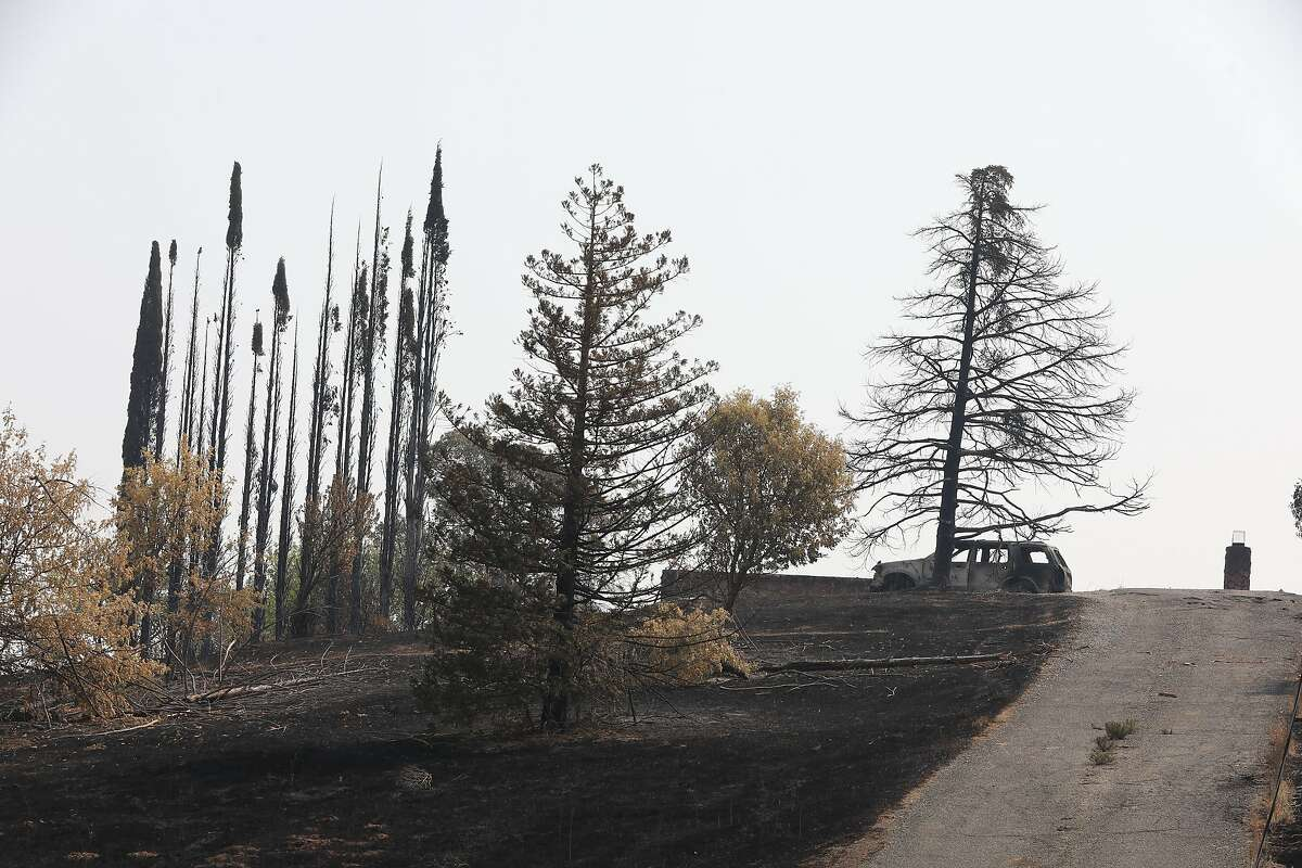 Charred remains of a vehicle are left vacant in a driveway off of English Hills Rd. following a wildfire in Vacaville, Calif., on Wednesday, August 25, 2020.