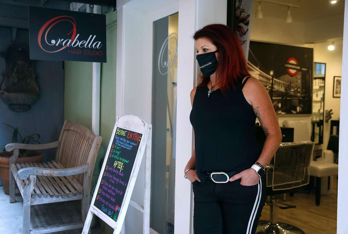 Alicia Orabella stands in the doorway of her hair studio in Oakland, Calif. on Wednesday, Aug. 26, 2020. Orabella has decided against reopening her small studio when Alameda County loosens restrictions on hair salons Friday allowing them to operate outdoors only.