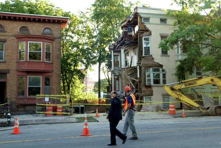 Albany Fire Chief Robert Forezzi Sr., left,  walks by 600 Madison Ave., right, where a wall collapsed on Friday, Aug. 27, 2010, in Albany. (Cindy Schultz / Times Union) Photo: Cindy Schultz