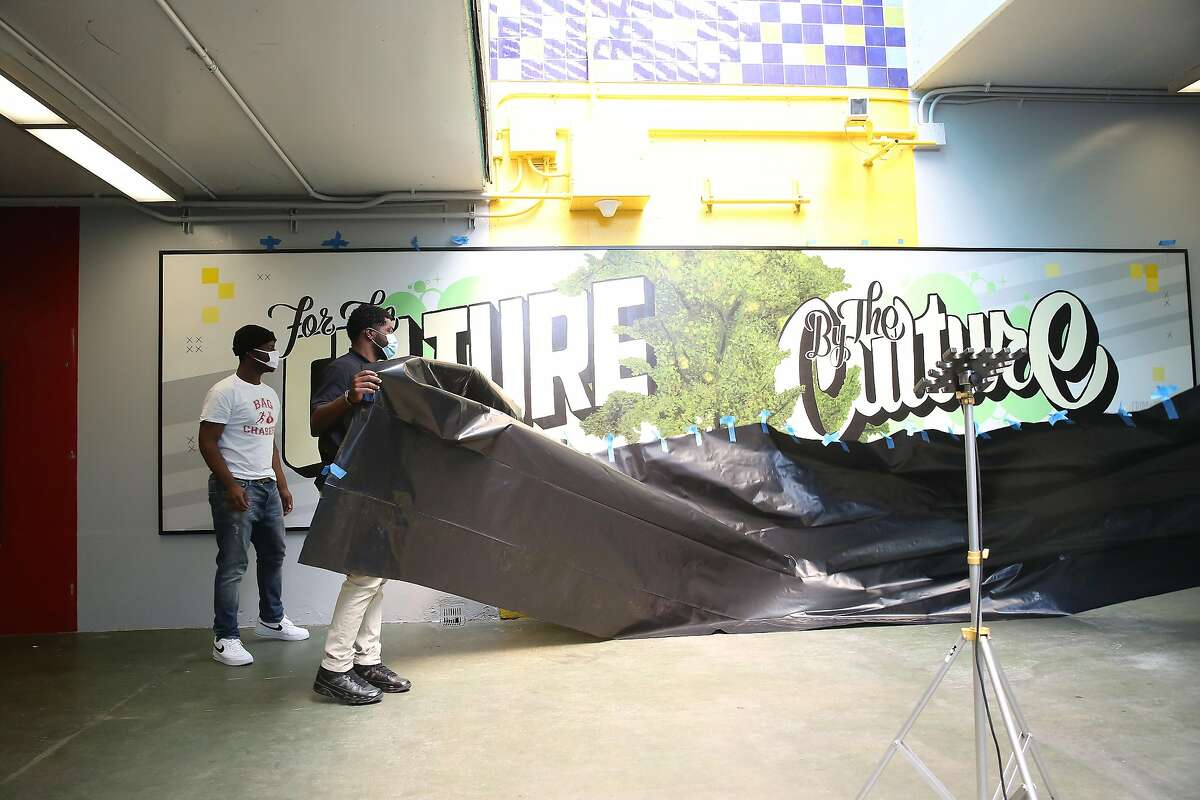 """BART interns Jordan Hill (l to r) and Hezekiah Pemberton help unveil the mural """"For the Culture, By the Culture"""" at the Coliseum BART Station on Friday, August 21, 2020 in Oakland, Calif."""