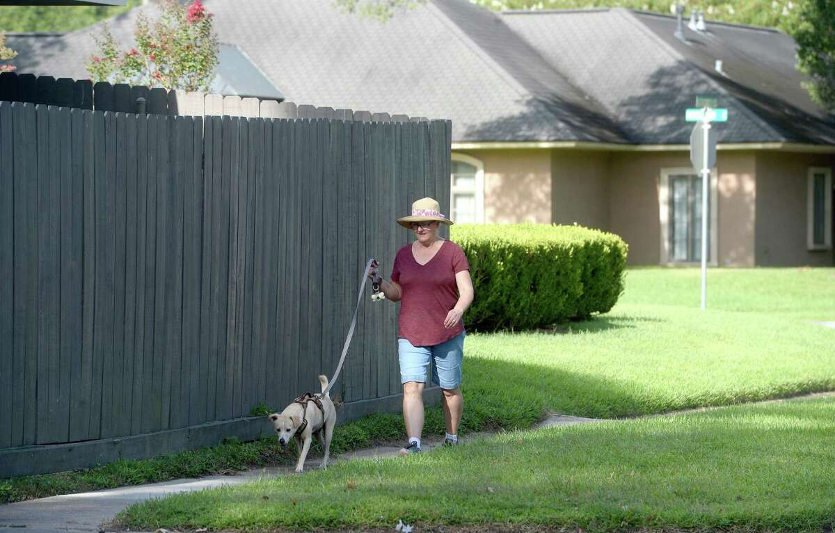 Beverly Aulbaugh walks her dog Lucky in Beaumont Wednesday as residents evacuate or make final preparations to ride out the storm. Aulbaugh says her family is staying at their home, as she has an elderly father living with them that makes it simply too difficult to evacuate. She says they have a generator to ride out the power loss that is expected. Photo taken Wednesday, August 26, 2020 Kim Brent/The Enterprise