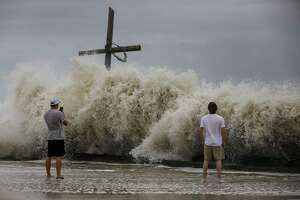 Mark Allums, left, and Hunter Clark watch waves crash ashore as outer bands from Hurricane Laura begin to hit the coast Wednesday, Aug. 26, 2020, in High Island. The two are from Bogata, Texas, near Paris, Texas, and they came to board up windows at a beach house in High Island.