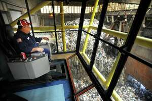 Overhead crane operator Luis Rullan guides a giant claw to pick up trash at Wheelabrator's Bridgeport Resco waste-to-energy plant in Bridgeport in 2013.