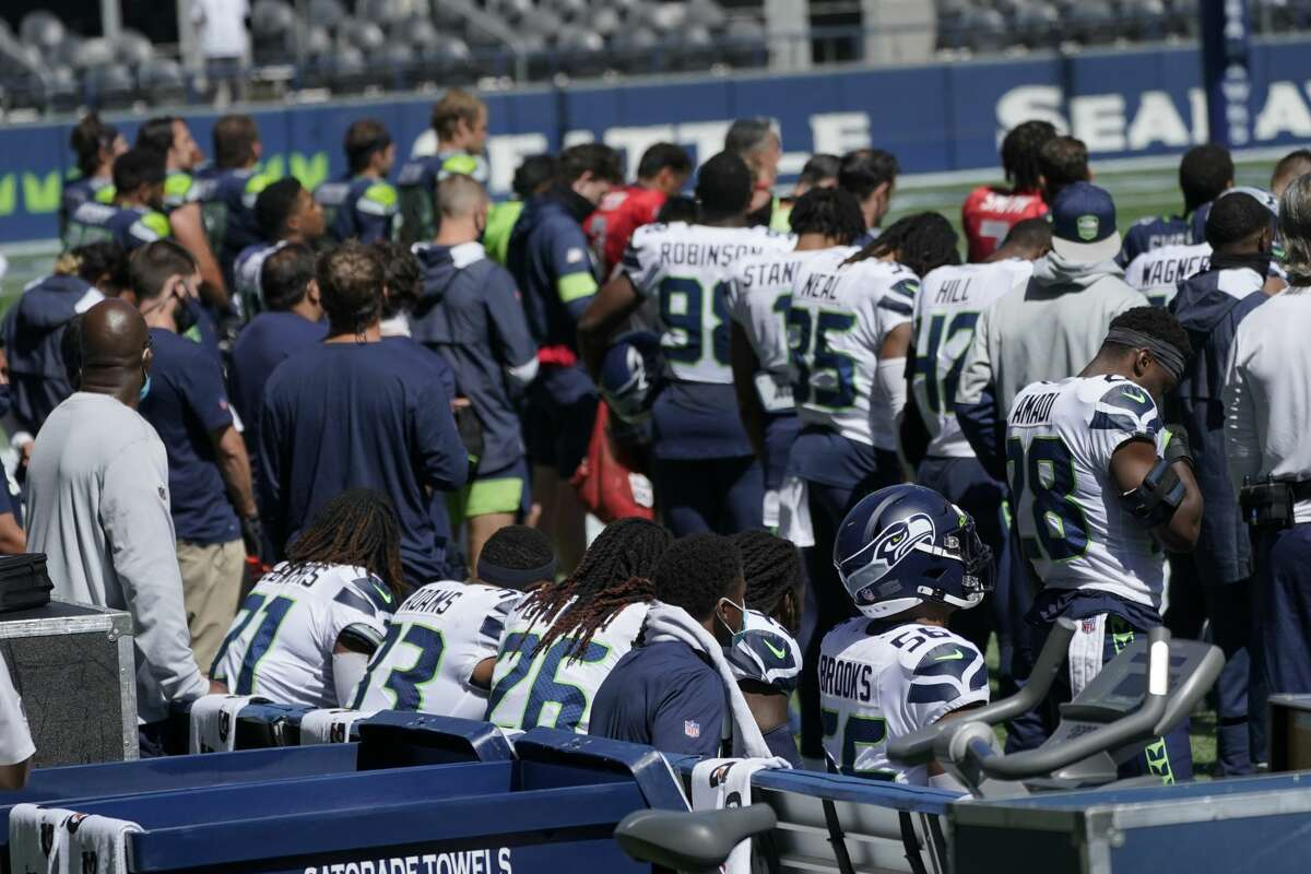 Seattle Seahawks players (seated from left) Tre Flowers, Jamal Adams, Shaquill Griffin, Shaquem Griffin, and Jordyn Brooks sit on the bench during the singing of the national anthem before an NFL football mock game, Wednesday, Aug. 26, 2020, in Seattle. (AP Photo/Ted S. Warren)