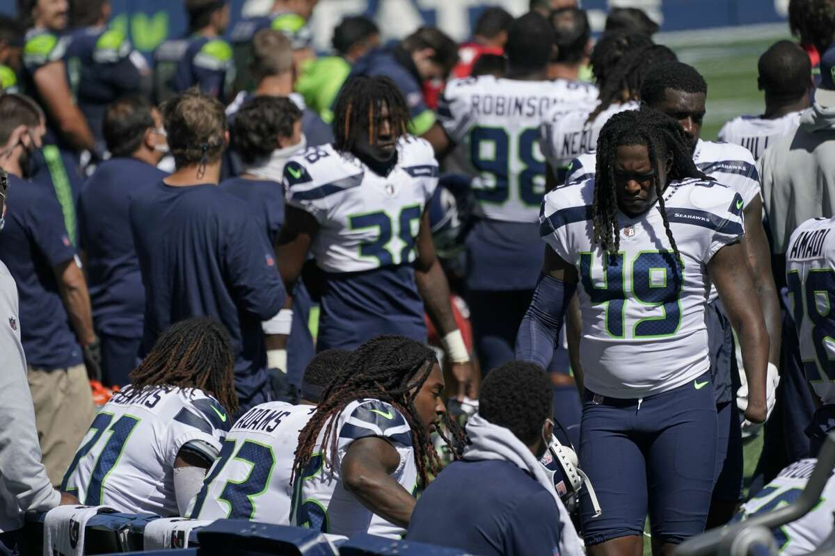 Seattle Seahawks linebacker Shaquem Griffin (49) walks to sit on the bench next to teammates, including his brother, cornerback Shaquill Griffin, third from lower-left, during the playing of the national anthem before an NFL football mock game, Wednesday, Aug. 26, 2020, in Seattle. (AP Photo/Ted S. Warren)
