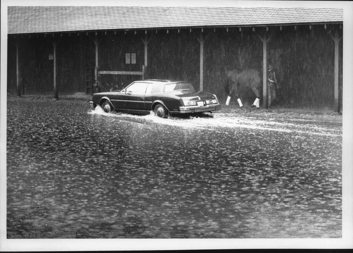 Water Water Everywhere -- Car drives through a mini lake alongside barn 9 on the back stretch at Saratoga Race Course, New York. The person walking the horse might be thinking of building an ark. August 29, 1988 (Paul D. Kniskern/Times Union Archive)