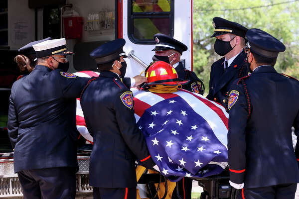 Converse Fire Chief Luis Valez, left, places the helmet of Converse Fire Captain, Chief Bryant Anderson who died of COVID-19, on Anderson's flag-draped coffin as it is taken from an ambulance with honors by a Converse Fire Department Guard on Friday, Aug. 5, 2020.