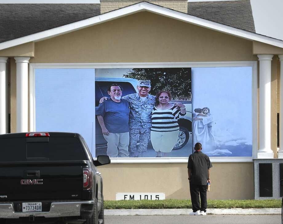 A friend of Tomas Morales stands in front of the large tv screens watching the memorial slideshow in memory of Morales at Mission Park Funeral Chapels South, on Friday, July, 17, 2020. Photo: Bob Owen / ©2020 San Antonio Express-News