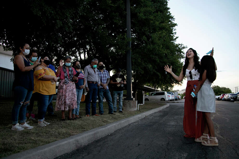 Susie Medrano, with daughter Alexis Martinez, sings at the conclusion of a prayer for Nora, her great-aunt, July 23 outside San Antonio's Southwest General Hospital. Nora's husband and four children were joined by others in praying for her for close to an hour. Photo: Lisa Krantz/Staff Photographer / San Antonio Express-News