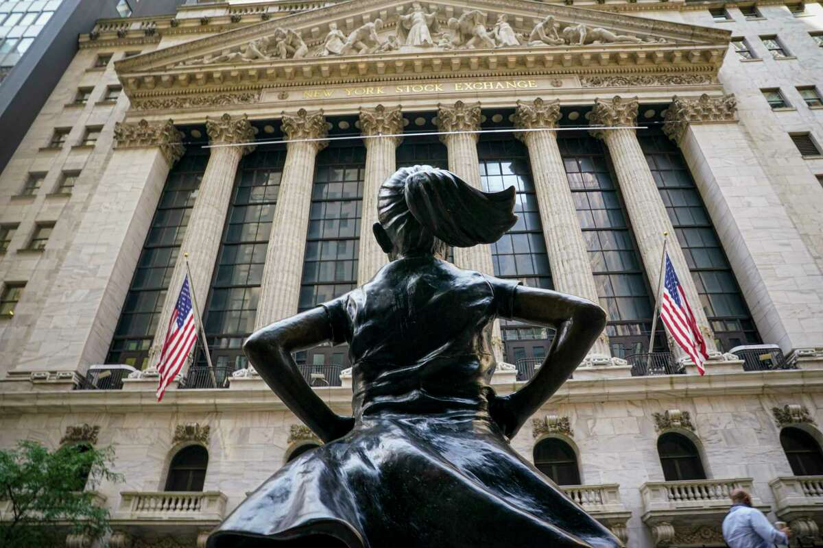 The 'Fearless Girl' bronze sculpture looks towards the New York Stock Exchange from its roadside perch, Tuesday Aug. 25, 2020, in New York. Most stocks are opening lower on Wall Street Wednesday, a day after the S&P 500 set its latest record high, but gains from several big technology companies and other stocks nudged the index slightly higher in the early going. (AP Photo/Bebeto Matthews)