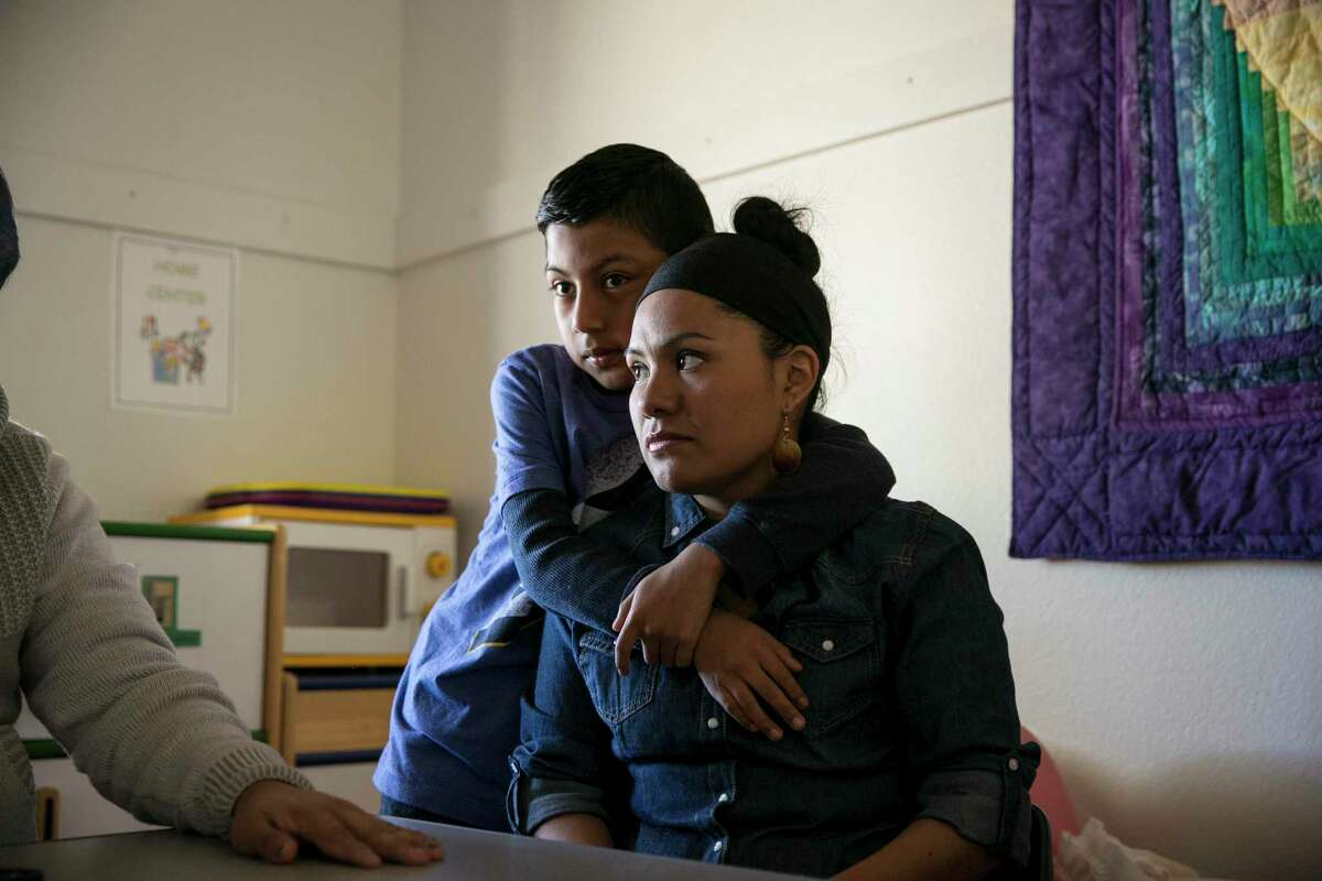 Ivan Ramirez, 10, embraces his mother, Hilda Ramirez, at St. Andrews Presbyterian Church in Austin. In one of his first acts as president, Trump ordered Homeland Security to look at withholding federal funding from cities that refuse to assist immigration officials. MUST CREDIT: Ilana Panich-Linsman for The Washington Post. Photo by:Ilana Panich-Linsman-For The Washington Post