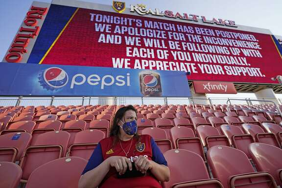 A fan sits in the stands after the scheduled game between Real Salt Lake and Los Angeles FC was postponed Wednesday, Aug. 26, 2020, in Sandy, Utah. Major League Soccer players boycotted five games Wednesday night in a collective statement against racial injustice. The players' action came after all three NBA playoff games were called off in a protest over the police shooting of Jacob Blake in Wisconsin on Sunday night. (AP Photo/Rick Bowmer)