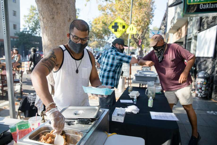 (Left to right) Mario Camargo of Blake's Grillery prepares tacos while his partner, Chris Parks, says hello to customer D.G.Blackburn. Blake's Grillery helps bars with patios fulfill the requirement to become restaurants. They were serving tacos to customers at the Avenue on Temescal Avenue on Aug. 19, 2020 in Oakland, Calif. Photo: Douglas Zimmerman/SFGATE / SFGATE