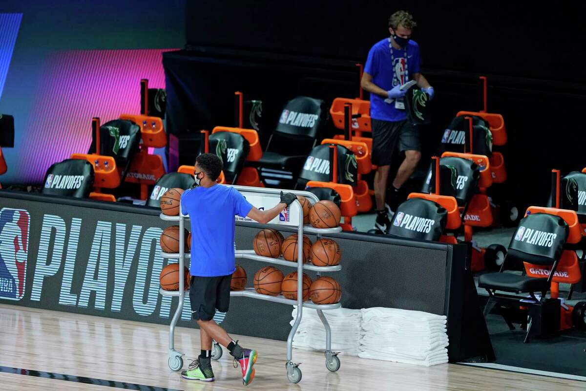 Workers clear items from the Milwaukee Bucks bench after the scheduled start time of an NBA basketball first round playoff game between the Milwaukee Bucks and the Orlando Magic, Wednesday, Aug. 26, 2020, in Lake Buena Vista, Fla. (AP Photo/Ashley Landis, Pool)