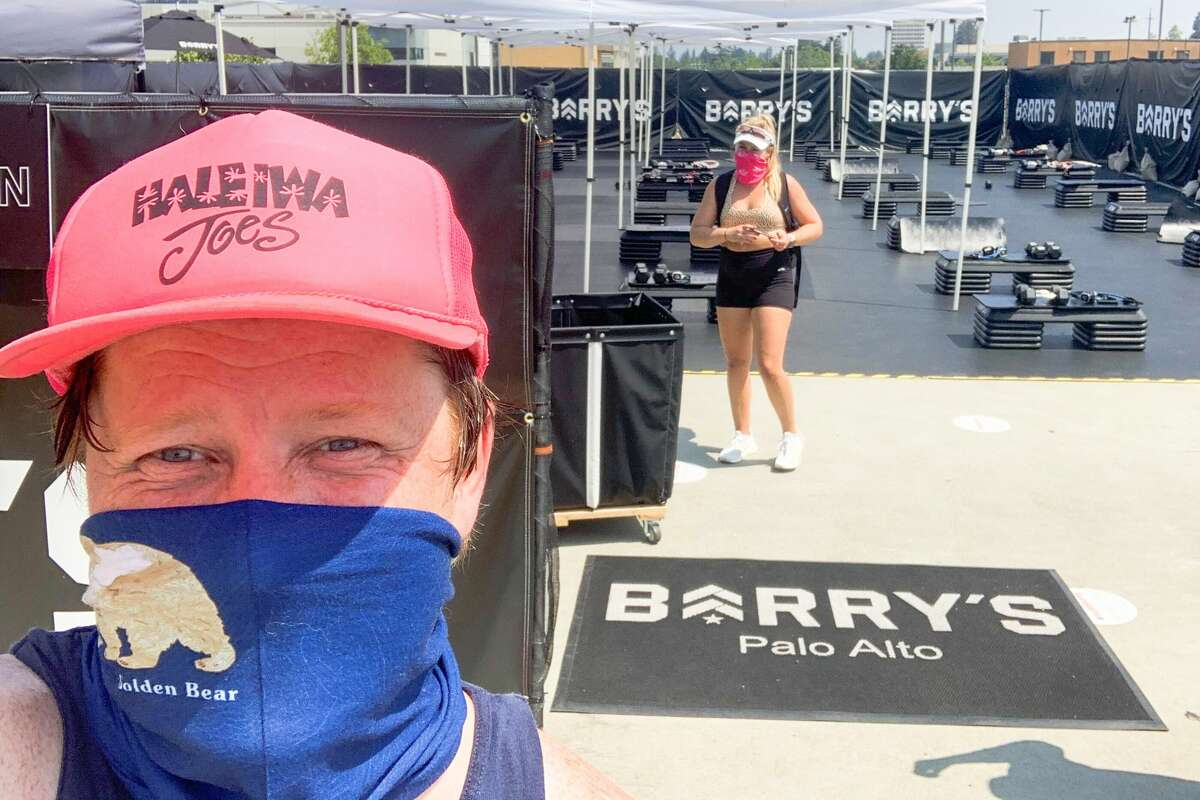 Grant Marek takes part in a Barry's Bootcamp class at the company's Palo Alto location on top of the Stanford Shopping Center rooftop parking lot.
