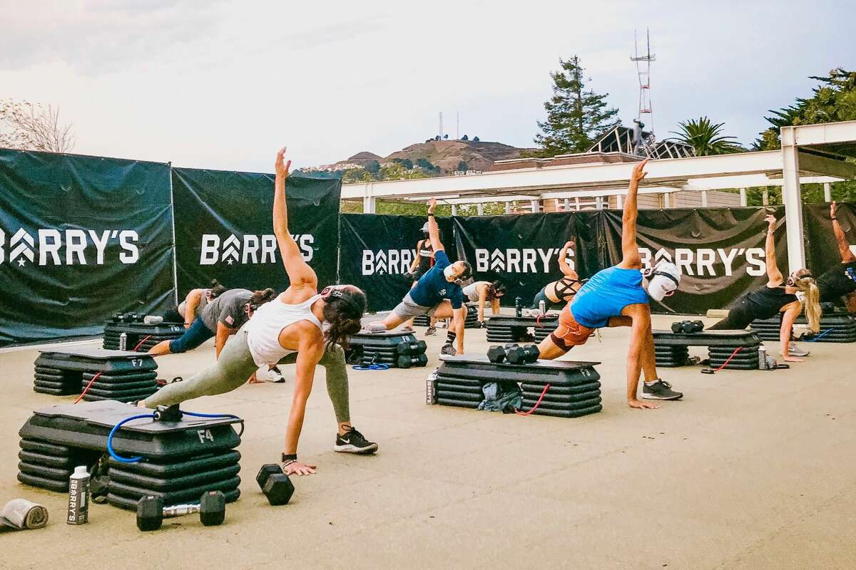 People take part in a Barry's Bootcamp outdoors class at the Castro rooftop car lot in San Francisco.