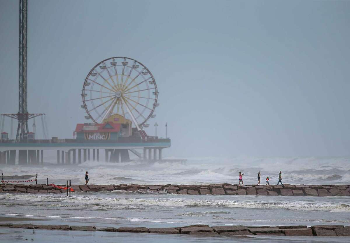 GALVESTON, TX - AUGUST 26: People walk along a jetty as waves roll in from approaching Hurricane Laura on August 25, 2020 in Galveston, Texas. Laura rapidly strengthened to a Category 4 hurricane during the day, prompting the National Hurricane Center to describe the accompanying storm surge as