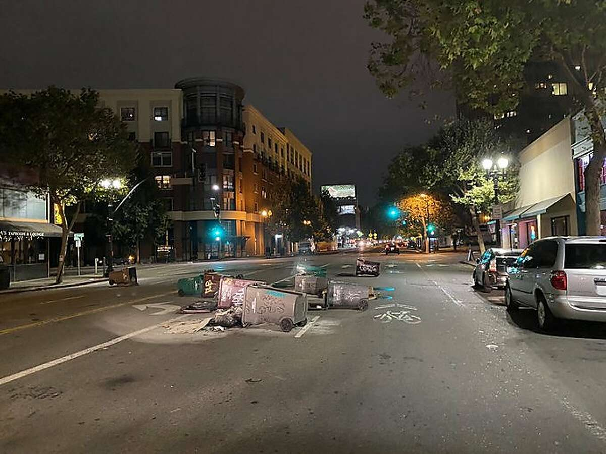 Photos and video shared on the Oakland Police Department Twitter page shows tipped over trashcans sprawled in the middle of the street, and two small fires surrounded by traffic cones on Wednesday, Aug. 26, 2020. Police said officers and firefighters were responding to multiple reports of trashcans set ablaze and fireworks set off after a demonstration in Oakland Wednesday night.