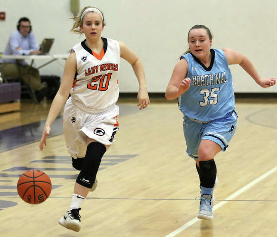 Gillespie's Grace Bertolino (left) rushes the ball upcourt past North Mac's Claire Harvey during a Macoupin County Tournament game last year in Mount Olive. Next school year, North Mac will join Gillespie as a member of the South Central Conference. Photo: Telegraph File Photo