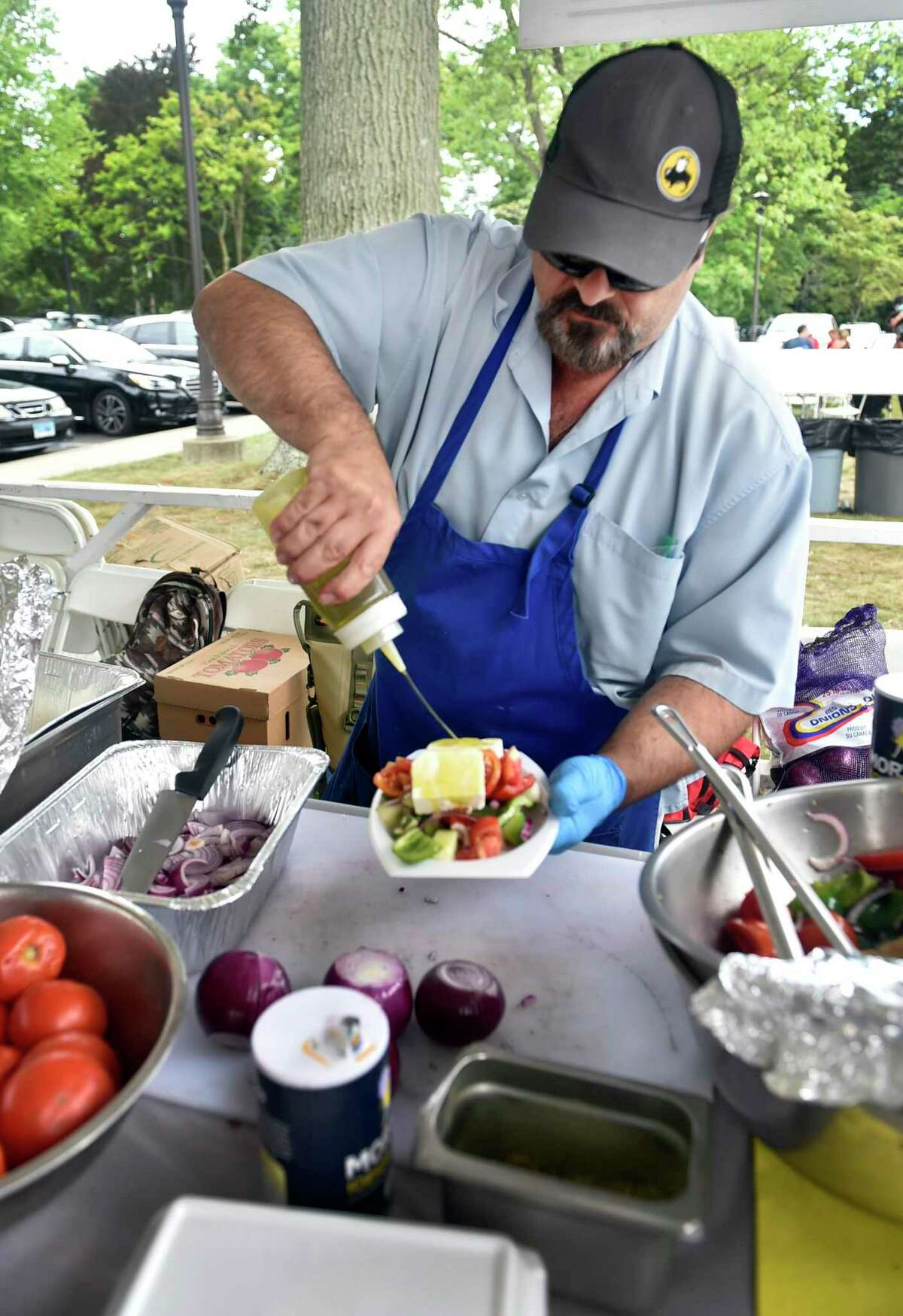 Jim Bitzomis of Stamford prepares a Horiatiki, a Greek peasant salad, available for pickup Sept. 5 and 6.