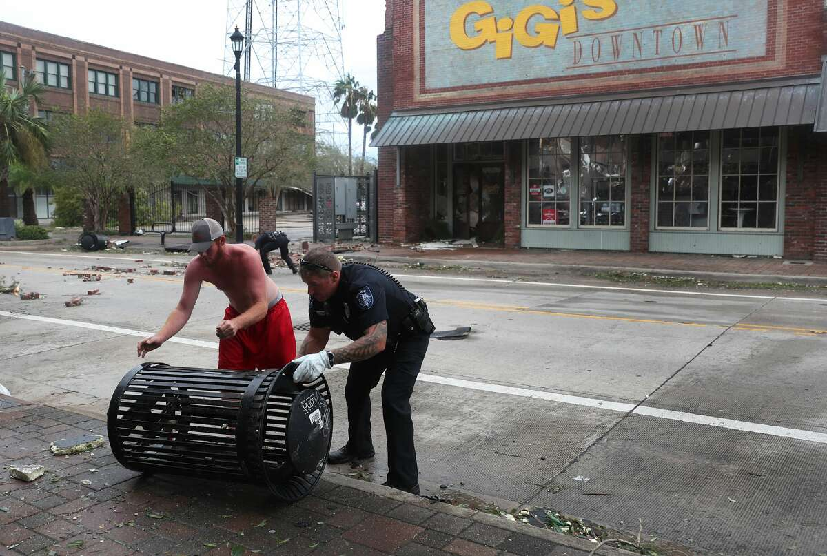 A Lake Charles police officer helps clear the streets in the downtown area after Hurricane Laura passed through on August 27, 2020 in Lake Charles, Louisiana . The hurricane hit with powerful winds causing extensive damage to the city. (Photo by Joe Raedle/Getty Images)